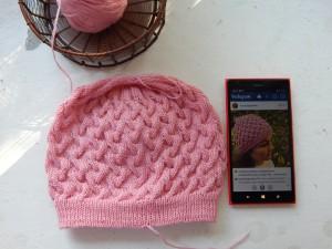 розовая шапка рядом с телефоном