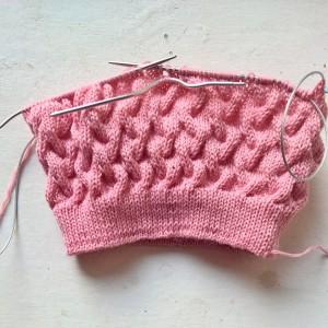 розовая шапка с косами в процессе
